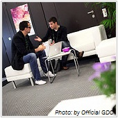 two businessmen sitting on a couch and talking